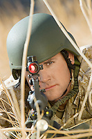 Soldier aiming rifle hiding in long grass (close-up)