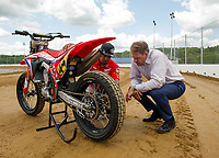 Cameron Smith and Governor Chris Sununu look over Smith's Honda CRF45OR race bike during Thursday's press conference at the North East Motor Sports Museum and Flat Track in Loudon. (Karen Bobotas/for the Laconia Daily Sun)
