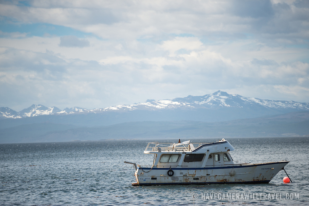 A well-worn private boat is anchored in Ushuaia Harbor in front of the Beagle Channel. The snow-capped mountains in the distance are across the Beagle Channel in Chile.