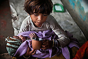 A young girl is caring for her newborn sibling while drinking Indian chai tea for breakfast in the impoverished Oriya Basti colony, in Bhopal, Madhya Pradesh, India, near the abandoned Union Carbide (now DOW Chemical) industrial complex, site of the infamous 1984 gas tragedy. The poisonous cloud that enveloped Bhopal left everlasting consequences that today continue to consume people's lives.