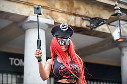 © Licensed to London News Pictures. 04/08/2018. LONDON, UK. A woman sits on top of a Lamborghini Aventador parked up in Covent Garden for Gumball 3000, a charity race for supercars and more.  150 cars will journey from London to Tokyo in a race which commences on Sunday 5 August.  Photo credit: Stephen Chung/LNP