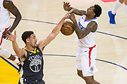 Golden State Warriors guard Klay Thompson (11) fouls LA Clippers guard Lou Williams (23) during a shot attempt at Oracle Arena in Oakland, California, on February 22, 2018. (Stan Olszewski/Special to S.F. Examiner)