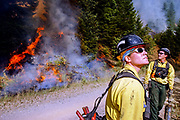 """Hotshots battling a wildfire in Tiller, Oregon back in 2002. Global warming triggers ever more and bigger wildfires. For the first time in its 110-year history, the Forest Service, part of the U.S. Department of Agriculture, is spending more than 50 percent of its budget to suppress the nation's wildfires, according to a report released  August 5th 2015. """"Climate change and other factors are causing the cost of fighting fires to rise every year,"""" said Agriculture Secretary Tom Vilsack, """"but the way we fund our Forest Service hasn't changed in generations.» The work done by hotshots and smoke jumpers is extremely dangerous, trying to contain and control the fire by cutting or burning off fuel on the ground. They are in good physical condition and have to be able to take care of themselves in case they get trapped by the unpredictable fires."""