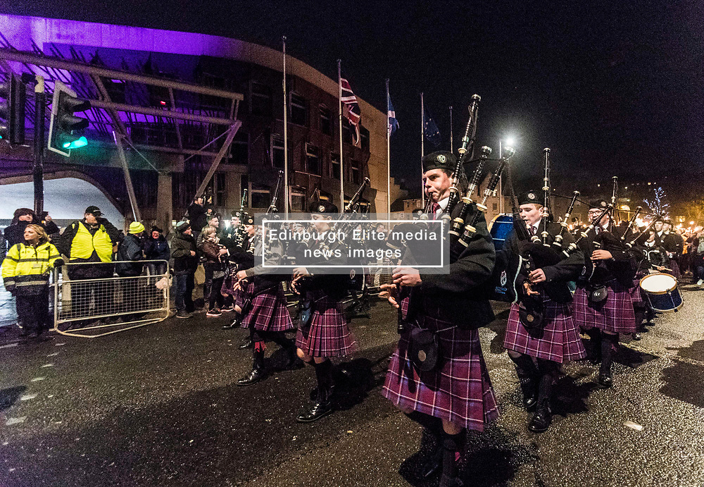 Edinburgh's Hogmanay celebrations start with the traditional torchlit procession. This year the route finishes outside the Scottish Parliament in  Holyrood where a word chosen by the young people of Scotland that makes them proud to live in the country is revealed by the thousands of torch bearers.<br /> <br /> Pictured: Pipe band leading the torchlit procession in front of the Scottish Parliament