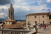 Tourists outside Cathedral of Saint Mary of Girona, Catalonia, Spain. Basilica Parroquial de Sant Feliu in the background