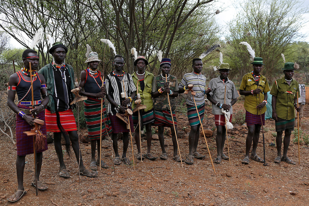 Pokot men stand near the home of a girl to be taken as wife for a member of their group.