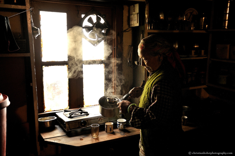 An old women is preparing tea at the kitchen of her home at the Tibetan settlement in Manali, India, 2009