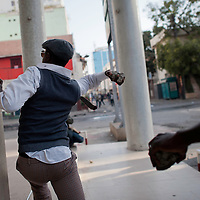 A Man throws a stone against the police during protest in Dakar on February 18, 2012. Senegal riot police clashed with rock-throwing protesters today, firing teargas and water cannon for the fourth day running as fresh violence hit the capital a week before highly divisive polls. The opposition has been banned from protesting in central Dakar, leading to a second day of cat-and-mouse battles with police in the seaside capital who were trying to prevent them from gathering at Independence Square.