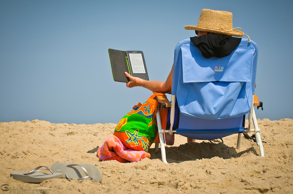 Person reading a book on a Kindle tablet device at the beach..