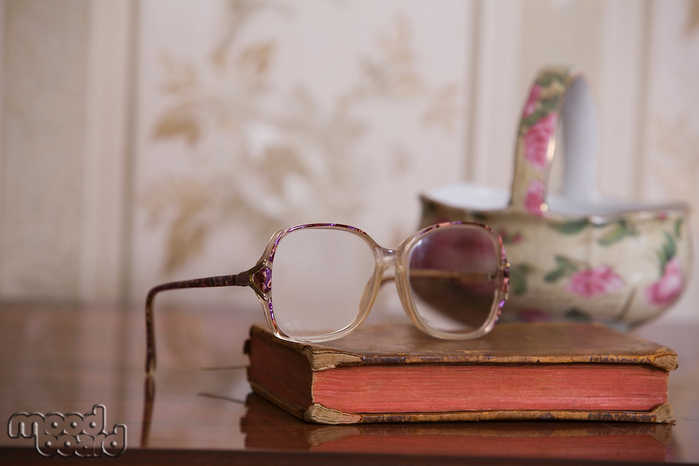 Spectacles on hardbacked book with china bowl