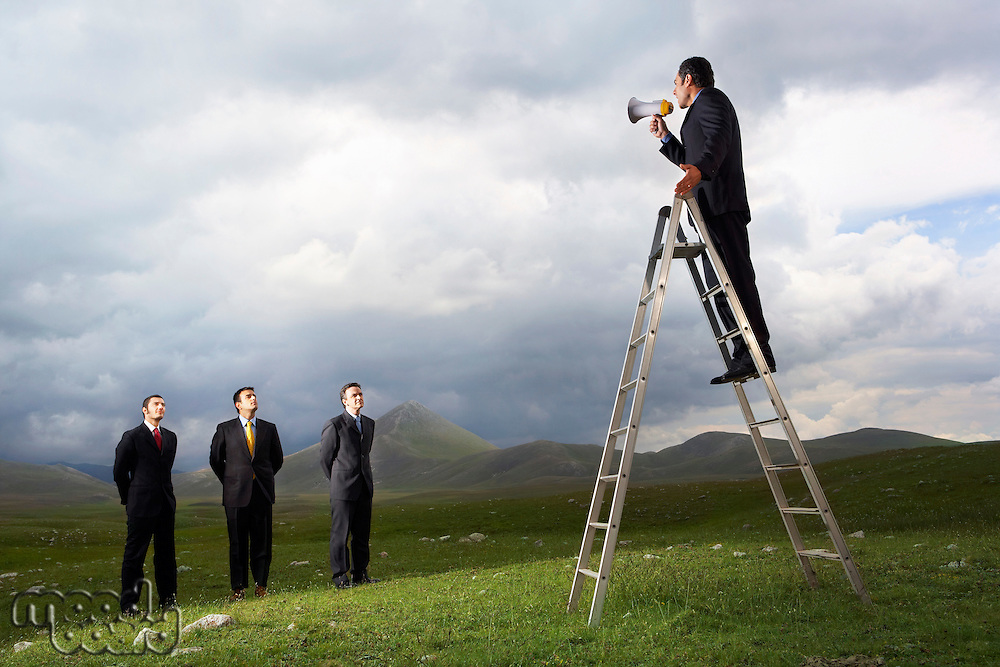 Businessman in mountain field Speaking Through Megaphone to other businessmen full length