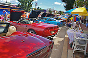 Historic cars including red Corvette convertables in foreground are viewed by visitors to the antique car show on Main Street, Millville, New Jersey