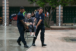 September 10, 2017 - St. Petersburg, Florida, U.S. - EVE EDELHEIT   |   Times.(from left to right) Firefighters Dohnovan Simpson and Jacob McGovern carry Dolores Gevaza, 83, (Center) across the courtyard in the rain at John Hopkins Middle School on Sunday, September 10, 2017 in St. Petersburg. The school filled classrooms and hallways with  people evacuating before Hurricane Irma makes landfall. The shelter welcomes people from the area with pets and those with special needs. (Credit Image: © Eve Edelheit/Tampa Bay Times via ZUMA Wire)