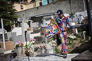 Un integrante de los Diablos de Naiguatá camina sobre la tumba de un familiar durante la festividad del Corpus Christi, representada en Venezuela a traves del ritual magico-religioso de los Diablos Danzantes. Los Diablos de Naiguata se identifican por pintar sus propios trajes y decorarlos con cruces, rayas y circulos, figuras que impiden que el maligno los domine. Las mascaras son en su gran mayoria animales marinos. Llevan escapularios cruzados, crucifijos y cruces de palma bendita. Naiguata, 30 Mayo 2013. (ivan gonzalez)