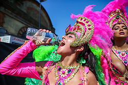 © Licensed to London News Pictures. 26/08/2019. London, UK. A dancer drinks water on a very hot day during the  Notting Hill Carnival in west London. Thousands of revellers take part in Notting Hill Carnival, Europe's largest street party and a celebration of Caribbean traditions and the capital's cultural diversity. Photo credit: Dinendra Haria/LNP