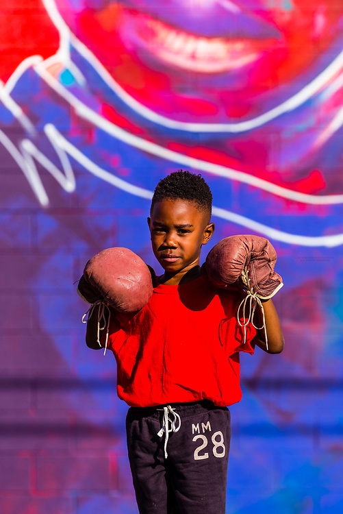 """5 year old Britton Grae-Chapman with boxing gloves in front of a huge mural painted of him by a local artist known as """"Detour"""" (actual name Thomas Evans), Denver, Colorado USA."""