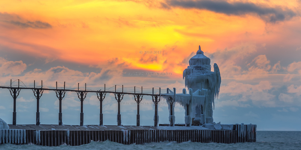 Blazing clouds set on fire by the setting sun creates a stark contrast to the ice-covered outer beacon on the north pier in St. Joseph, Mi