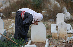September 1, 2017 - Nablus, West Bank, Palestinian Territory - A Palestinian woman visits the grave of her relative at a cemetery on the first day of Eid al-Adha, or feast of the sacrifice, in the West Bank village of Lubban Ash-Sharqiya near Nablus. Muslims around the world are celebrating Eid al-Adha, the ''Feast of Sacrifice'', which marks the end of the annual pilgrimage or hajj to the Saudi holy city of Mecca and in remembrance of Abraham's readiness to sacrifice his son to God  (Credit Image: © Ayman Ameen/APA Images via ZUMA Wire)