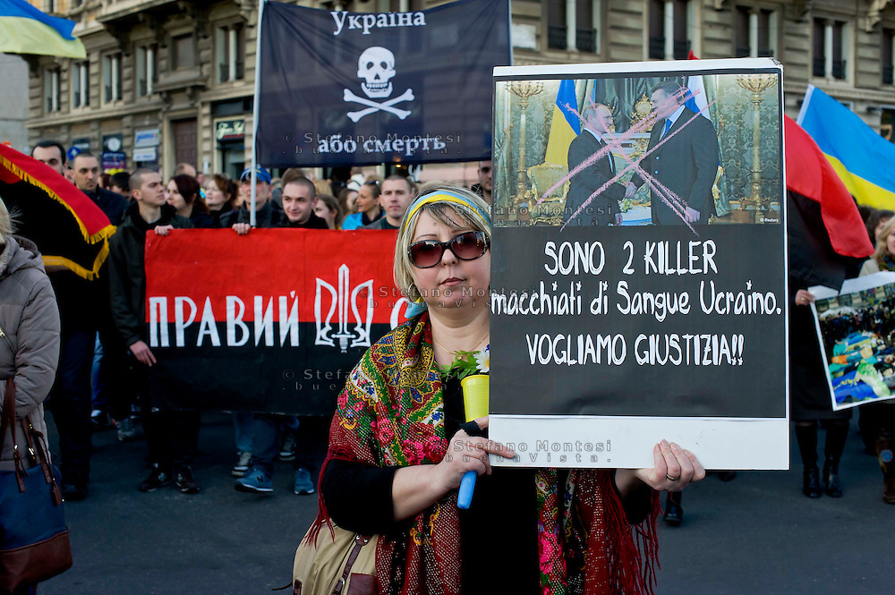 Roma 23 Febbraio 2014<br /> Manifestazione nazionale della comunit&agrave; ucraina in Italia per  ricordare i morti degli scontri dei giorni scorsi a Kiev e contro la dittatura del presidente  Yanukovych.Manifestante con un cartello contro Putin e Yanukovych<br /> Rome 23 Febraury  2014<br /> National demonstration of the Ukrainian community in Italy to commemorate the dead of the recent clashes in Kiev and against the dictatorship of President Yanukovych.Protestor with a sign against Putin and Yanukovych
