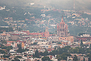 Morning fog rises over the colonial center and city landmark Parroquia de San Miguel Arcángel church in San Miguel de Allende, Mexico at dawn.