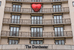 "© Licensed to London News Pictures. 14/02/2018. LONDON, UK. A giant chubby heart balloon is seen The Dorchester Hotel as part of ""Chubby Hearts Over London"",  a design project conceived by Anya Hindmarch.  Supported by the Mayor of London, the British Fashion Council and the City of Westminster giant chubby heart balloons will be suspended over (and sometimes squashed within) London landmarks as a declaration of love to the city starting on Valentine's Day and continuing throughout London Fashion Week.   Photo credit: Stephen Chung/LNP"