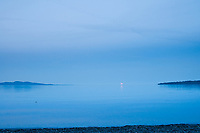 The ocean and sky are blue at dusk at the beach at Cordova Bay near Victoria, BC