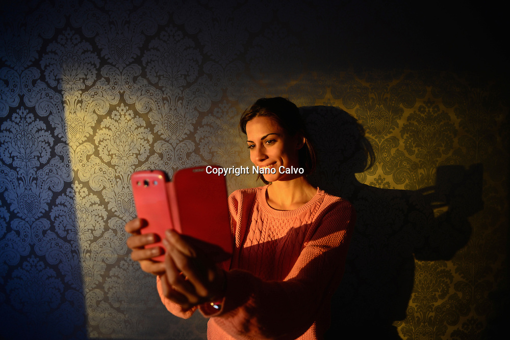 Young woman takes a selfie with mobile phone in hotel room, Kemi, Lapland