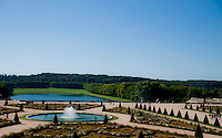 Palace of Versailles. Wide view of the gardens seen through old glass.