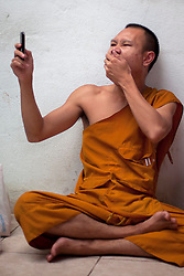 A Buddhist monk take a picture with his phone while yawn at Wat Bang Phra Temple in  Nakhon Pathom province, Thursday, March. 02, 2012.