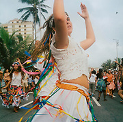 Female dancer wearing a white outfit, dancing in the street during a carnival Brazil