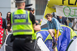© Licensed to London News Pictures. 17/07/2019. Leeds, UK. Police watch a protester get dressed this morning as the Extinction Rebellion protest enters its third day in Leeds where activist's have blocked Victoria Bridge in the city centre with a boat & tents. The protest is part of Extinction Rebellion's 'summer uprising' campaign, which has seen similar blockades in London, Cardiff, Bristol and Glasgow & is expected to last until Friday. Photo credit: Andrew McCaren/LNP