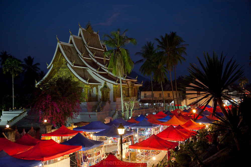 Night market with the Vat Mai Buddhist Temple in the background in Luang Prabang, Laos.