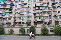 Woman riding an electric bike by an apartment building in Hangzhou, China 2009.