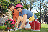 Two women planting flowers in garden