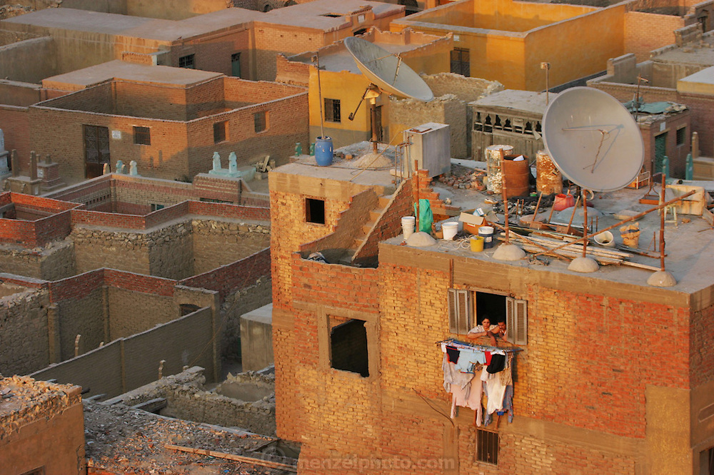 Couple looking out the window of their apartment above hanging laundry in Cairo, Egypt. Bordering the city of the dead.