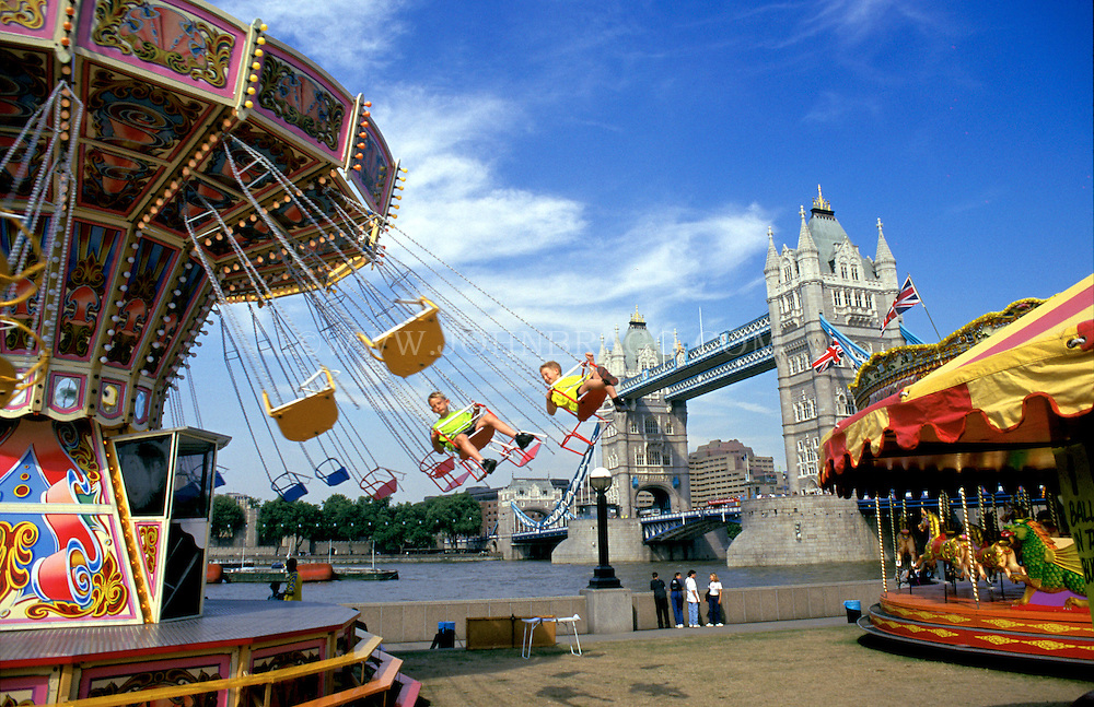 Photo of carnival rides along the Thames river by the Tower Bridge in London, England