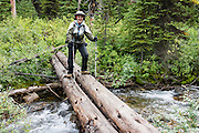"""Carol crosses Chalice Creek on a primitive log bridge in Bugaboo Provincial Park, in the Purcell Range of the Columbia Mountains, British Columbia, Canada. Most tourists are attracted by nearby Canadian Rockies parks along fast paved highways and skip gravel logging roads, thereby leaving the spectacular """"Bugaboos"""" as a quiet retreat for hikers, climbers, and luxury CMH helicopter guests. Directions: From Brisco (about 44 kms north of Invermere on Hwy 95), follow signs to Bugaboo Provincial Park and CMH Lodge on a gravel logging road. After 47 kms, turn right on a rougher road to reach Cobalt Lake trail head and Kain Hut trail head, or continue straight along Bugaboo Forest Service Road. Before you reach the gate of luxury CMH Bugaboo Lodge, a left turn crosses Bugaboo Creek bridge: then a left reaches Bugaboo Septet Recreation Site (4 primitive campsites in a free, user-maintained campground reachable by 2WD vehicles) or straight up takes 4WD vehicles and hikers to Chalice Creek trailhead."""