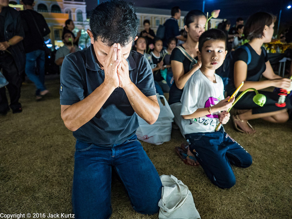 20 OCTOBER 2016 - BANGKOK, THAILAND:   People in mourning for the death of Bhumibol Adulyadej, the King of Thailand, pray at the wall of the Grand Palace in Bangkok. Sanam Luang, the Royal Ceremonial Ground, is packed with people mourning the Monarch's death. The King died Oct. 13, 2016. He was 88. His death came after a period of failing health. Bhumibol Adulyadej was born in Cambridge, MA, on 5 December 1927. He was the ninth monarch of Thailand from the Chakri Dynasty and is also known as Rama IX. He became King on June 9, 1946 and served as King of Thailand for 70 years, 126 days. He was, at the time of his death, the world's longest-serving head of state and the longest-reigning monarch in Thai history.      PHOTO BY JACK KURTZ