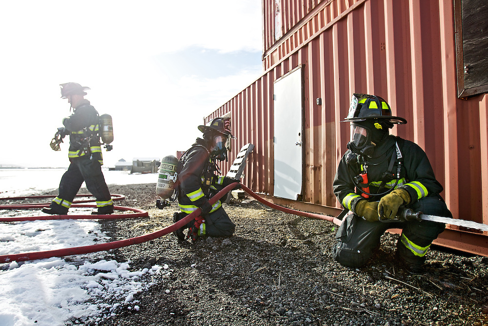 Northern Lakes firefighters Scott Hochberger, right, Cody Moore, center, wait to commence a practice routine inside the fire department's training tower Wednesday, Jan. 25, 2012 at the Coeur d'Alene Airport in Hayden, Idaho.