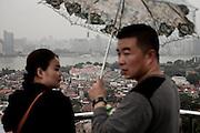 Un couple de jeunes touristes chinois contemple les demeures en contrebas sur l'ile de Gulangyu depuis le rocher Wanshi. A l'horizon la ville de Xiamen lancée dans la modernité.