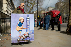 "© Licensed to London News Pictures. 13/03/2019. London, UK. Artist Kaya Mar holds a satirical painting of Prime Minister Theresa May outside Downing Street. MPs will vote on whether to remove the option of a ""no deal"" departure from the EU today, after Prine Minister Theresa May's proposed deal was defeated for a second time last night. Photo credit: Rob Pinney/LNP"