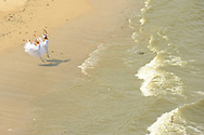 MR. Model relased photo. Two ballerinas dance and leap next to the Pacific Ocean on the beach.