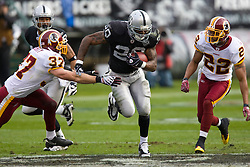 December 13, 2009; Oakland, CA, USA;  Oakland Raiders running back Darren McFadden (20) rushes past Washington Redskins safety Reed Doughty (37) during the first quarter at Oakland-Alameda County Coliseum.  Washington defeated Oakland 34-13.