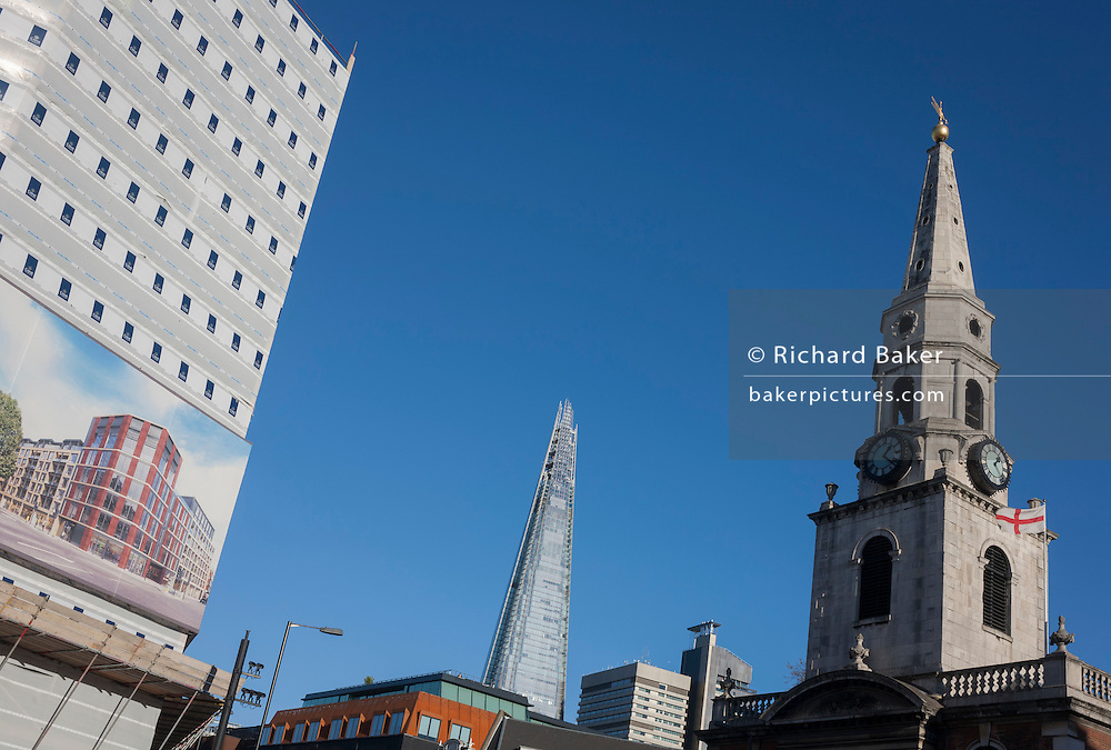 The new Shard tower rises high above London next to new housing and the spire of St George the Martyr church at Marshalsea, on 28th November 2016, in Borough, Southwark, England.