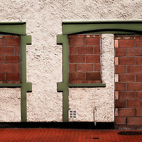 Filled in derelict door and widows with red brickwork