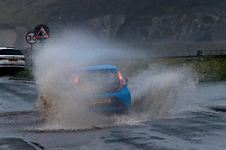 © Licensed to London News Pictures. 13/01/2020. Newgale, Pembrokeshire, Wales, UK. A motorist drives through a flooded road at Newgale in Pembrokeshire, Wales, UK. as Storm Brendan hits the South West coastline of  Wales, UK. Photo credit: Graham M. Lawrence/LNP