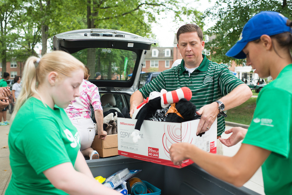 Vice President of Student Affairs Ryan Lombardi (Center Right) helps students move into their residence halls on East Green. Photo by Ben Siegel/ Ohio University