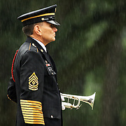 WILMINGTON, NC - JULY 9: A bugler stands at attention in the rain at the funeral of Sgt. 1st Class Edward Kramer in Wilmington, NC, on July 9, 2009. Kramer and three others died when an ied went off near the Humvee they were in, according to a statement from the defense department. It was the last day of regular combat operations for U.S. forces in Iraqi cities. The four deaths marked the North Carolina National Guard's largest single combat loss since World War II. (Photo by Logan Mock-Bunting/Getty Images)