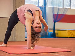 Woman bending over backwards in yoga position at athletics hall on tartan track, Offenburg, Baden-Wuerttemberg, Germany