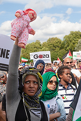 "London, August 9th 2014. A woman holds aloft a ""bloodstained"" doll as up to 150,000 people take part in a march and rally in support of the people of Palestine."